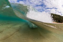 Small wave breaking over sandy beach at waimea bay hawaii Stock Photos