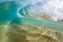 Under water view of Small wave breaking over sandy beach at waimea bay hawaii Royalty Free Stock Image