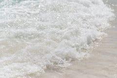 Small wave hitting sandy beach Stock Image