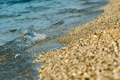 Small wave and sand. Small wave. White splashes, it's broken about seashore royalty free stock image