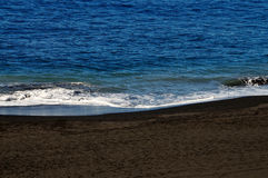 Small waves black sand beach Royalty Free Stock Images
