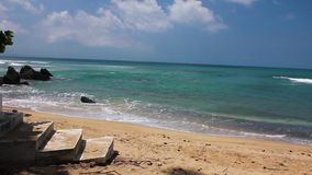 Small waves of clear tropical water hitting sandy beach in front of cement steps. Secluded beach on north shore of Vieques island, Puerto Rico. Crystal clean stock video footage