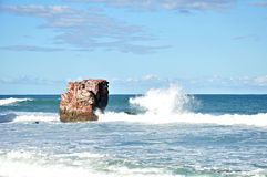 Small waves lapping on the rocks in blue sea Royalty Free Stock Images