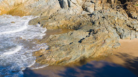 Small waves and rocky coast. Small waves lap against a rocky shoreline in 1770, Queensland, Australia Stock Photo