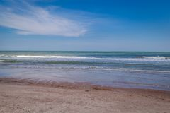 Small waves rolling onto the beach at Amelia Island. Waves coming ashore on a sunny day on Amelia Island Florida royalty free stock photo