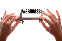 Small weakness. Color horizontal shot of two hands holding a caliper and measuring the word weakness Stock Photo