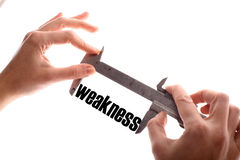 Small weakness. Color horizontal shot of two hands holding a caliper and measuring the word weakness Stock Photos