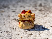 Old weathered lucky cat figure. A small weathered lucky cat figurine sits on a residential wall, where it seems to have been sitting for a long time stock image