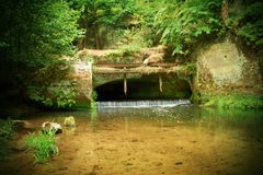 Small weir on river flows out from cave. Cold water of small river flow over small stony weir.  Stony and rusty construction of we. Small weir on the river flows Stock Photos