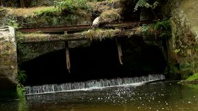 Small weir on the river flows out from cave. Cold water of small river flow over small stony weir. Stony and rusty construction of. Weir stock footage