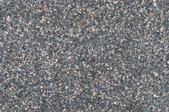 Small wet stones of different colors texture. Road texture of small colored stones wet after the rain on an overcast day Royalty Free Stock Image