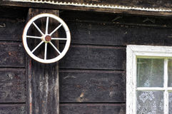 Small wheel fitted in the wall. Small wheel of cart fitted in wooden wall and netted window Royalty Free Stock Photo