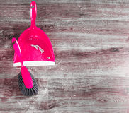 Small whisk broom and dustpan on wooden floor Royalty Free Stock Photography