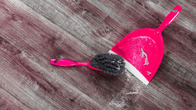 Small whisk broom and dustpan on wooden floor Stock Image