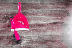 Small whisk broom and dustpan on wooden floor Royalty Free Stock Images