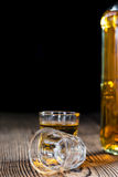 Small Whiskey shot. On an old wooden table Royalty Free Stock Photo
