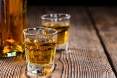 Small Whiskey shot. On an old wooden table Royalty Free Stock Photos