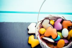 Small white basket full of candies easter eggs and rabbits pastel colors on slate board and blue wood. Copyspace royalty free stock images