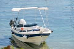 Small white blue motorized boat anchored on the shore. In Greece stock photography
