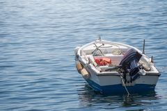 Small white blue motorized boat anchored on the shore. In Greece royalty free stock images