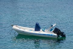 Small white blue motorized boat anchored on the shore. In Greece stock photos