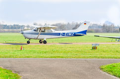 Small white blue sport aircraft during startup. View of the runway of the airport Essen-Mülheim. royalty free stock photography