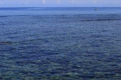 Small white boat adrift in a big blue sea Stock Image
