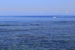 Small white boat adrift in a big blue sea Royalty Free Stock Photography