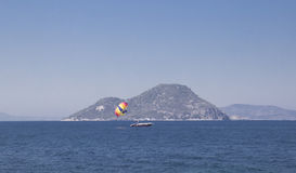 A small white boat on a deserted sea against a small island. In a cloudless summer day Stock Photography