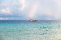 Small white boat on horizon on the sea. Rainbow and small white boat on the sea Royalty Free Stock Photo