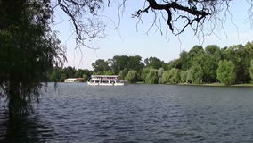 Small white boat. Small recreation boat floating on a park lake stock footage