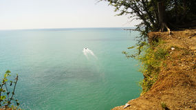 Small white boat sailing from the coast of the azure sea waters to the horizon. Small white boat sailing from the coast to the blue sea in the daytime under the Royalty Free Stock Images