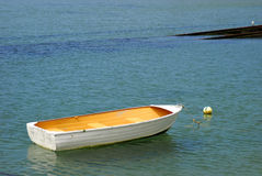 Small white boat. With yellow interior docked with buoy, seagull Royalty Free Stock Image
