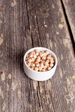 A small white bowl of dried organic garbanzo beans, vertical Royalty Free Stock Photography
