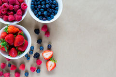 Small white bowls filled with ripe berries. Stock Photos