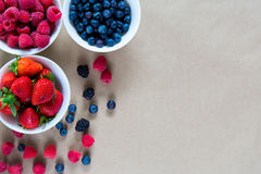 Small white bowls filled with ripe berries. Royalty Free Stock Image