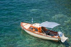 Small white brown wooden motorized boat anchored on the shore. In Greece royalty free stock photo