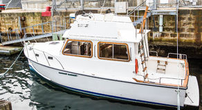 Small White Cabin Cruiser by Block Wall Stock Photos