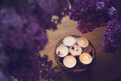 Small white candles in a basket and lilac Stock Image
