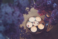 Small white candles in a basket, massage oil and essence. Surrounded by beautiful purple lilac stock photo