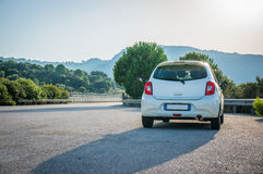 Small white car with led optics on the asphalt road highway. In sunrise Royalty Free Stock Images