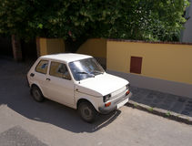 Small white car on medieval street. Small white car on a narrow street. Yellow fence, stone pavement of the curb Stock Image