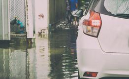 Small white car is traveling in a flooded street Royalty Free Stock Photography