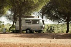 Small white caravan through the trees Royalty Free Stock Photo
