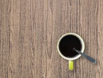 Small white ceramic coffee cup with black coffee and silver spoon on brown wooden table floor. Espresso flavor concentrate and aromatic keeping feeling fresh in Royalty Free Stock Photos