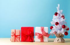Small white christmas tree with presents. On a blue background royalty free stock images