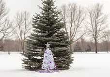 Small white christmas tree with purple and silver decorations standing in snow Stock Images
