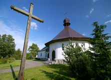 Small white church. With a wooden cross in the foreground Royalty Free Stock Photography