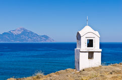 Small white church or chapel with holy mountain Athos in background Royalty Free Stock Photo