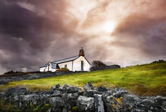 Small white church with cross and bell in dramatic cloudy sky Royalty Free Stock Photo